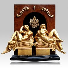 The Medici Cremation Urn is made from sapelle pomelle burl wood with black marble. The inserts and sculptures are in zamak and bronze with 18K gold plating.   Bottom opening panel.