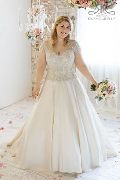 Romantic ball gown with natural waisted ornate beaded bodice, V- neckline front and back with beaded cap sleeves, set of with a full tafetta skirt. Roz la Kelin, Glamour Plus Collection Topaz 5851T.Plus size wedding dress available US,12-US,44.