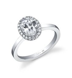 This elegant 18K white gold diamond engagement ring features a 0.75-carat round brilliant center diamond. Accentuated by surrounding round diamonds designed to enhance the center.
