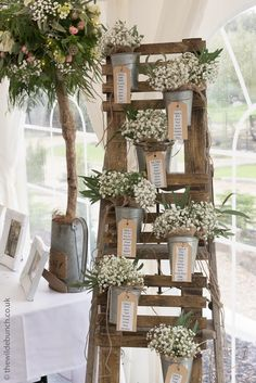 A simple, rustic Wilde Bunch table plan design. An old 1950's wooden decorators ladder and hanging pots filled with bunches of gypsophila that had previously adorned the aisle chairs. As designers we try and get the most out of of every bride's budget by re-using flowers as many times as possible through-out the Big Day.