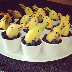 "I found these banana dolphin snacks for kids on Pinterest (couldn't find the original source) and they are ADORABLE! All you need to do is cut a banana in half, then cut a slit on the stem to make a ""mouth."" Stick a blueberry in its mouth and put it inside a plastic cup filled …"
