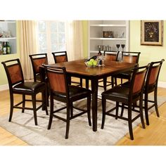 The two-toned counter height table has a unique inlaid wood table top, while the matching chairs also have acacia backs with padded leatherette seats. Acacia wood top gives this dining set a timeless look.