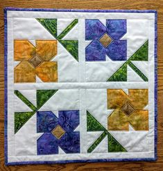 Brighten up your table for spring with this quilted table topper made with 100% cotton and batiks. The topper is a 21.25 inch square. The fabric used is quilt-store quality designer fabric. The reverse side is very light colored lavender striped. It are quilted with natural cotton