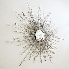 This lovely mirror has a design reminiscent of a starburst or sunburst design. The mirror is actually flanked by stems full of berries. The mirror is made with solid brass with a nickel plated finish.