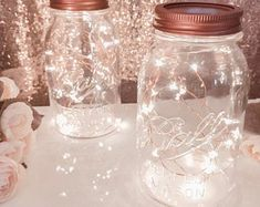 Mason jar centerpieces with floating candles. [UPDATED These DIY Mason Jar Centerpieces can also be made into favors. Use the lanterns to provide light to your wedding tables. Lantern With Fairy Lights, Mason Jar Fairy Lights, Mason Jar Lighting, Jar Lights, String Lights, Bottle Lights, Rustic Lantern Centerpieces, Wedding Centerpieces Mason Jars, Wedding Decorations