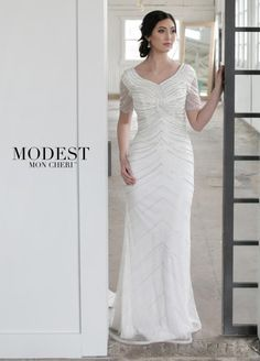 Style TR21855 from Mon Cheri Modest is a dazzling hand-beaded tulle sheath modest bridal gown decorated with sparkling crystals and hot stones that has modesty cap sleeves under beaded illusion short sleeves, a uniquely beaded bodice motif with a faux twist, a back concealed zipper, and a chevron beaded pattern skirt down to the thin horsehair hem and sweep train. Perfect for your garden wedding.