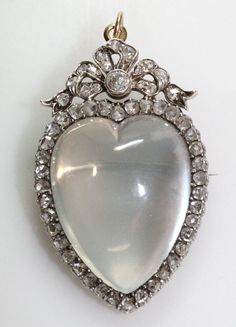 Large cabuchon moonstone rose diamond heart pendant surrounded by diamonds and set in silver and gold.
