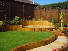 This sloped garden has curved landscaping with the slope held back with vertical wood panels. again, in-line with our thoughts but using sleepers landscaping slope railway sleepers Lush Garden, Terrace Garden, Garden Spaces, Dream Garden, Garden Beds, Home And Garden, Garden Edging, Hill Garden, Hillside Garden