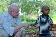 EGPAF President/CEO Chip Lyons gets to know a child while visiting a psychosocial support group for families affected by HIV. (Photo: EGPAF/Georgina Goodwin)