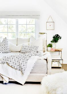 Cozy all-white living space with printed throw pillows and blankets