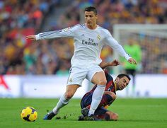 Cristiano Ronaldo of Real Madrid CF (L) is tackled by Xavi Hernandez of FC Barcelona during the La Liga match between FC Barcelona and Real Madrid CF at Camp Nou stadium on October 26, 2013 in Barcelona, Catalonia.