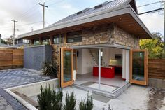 This is a modern 800 sq. ft. Laneway home in Vancouver. Outside, you'll notice a mixture of textures including a stone facade, grey concrete siding, and wooden accents. One of the coolest fea…