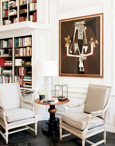 A small, built-in library close to a French-inspired sitting area with timeless armchairs and an abstract painting
