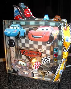 """""""Cars"""" glass block light - this one for my five year old grandson...he loves it!  Used the Disney Cars collection 3-D scrapbook stickers and a racing car sticker packet found at Hobby Lobby.  The Disney Cars ribbon and the Squinkies from Walmart."""