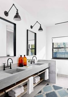 Black faucets + swing-arm lighting in the bath