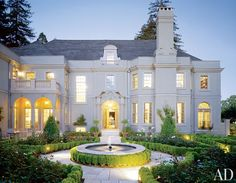 A parterre of roses surrounds a fountain at the entrance of a 1922 French-style mansion in Piedmont, California.