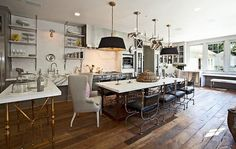 The open kitchen feels more like a seamless living space with upholstered furniture and drum shade pendant lighting.