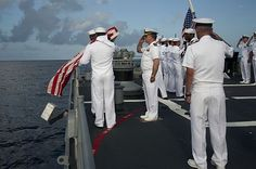 Fair winds Shipmate - Sailors assigned to the guided-missile cruiser USS Hue City  commit the remains of deceased Sailors to the sea during a burial-at-sea ceremony on the ship's fantail.