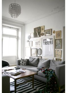 Interesting idea for hanging pictures...like how they extend below the back of the couch