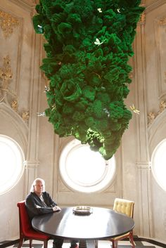 German lighting designer Ingo Maurer sitting beneath Biotope.