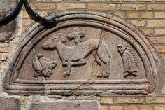Bjergby kirke: Granitrelieffer ·   Tympanon (døroverligger) over den nu tilmurede syddør. I midten et korslam (Kristus-symbol), til venstre en fugl (due = Helligånden) og til højre en person med håret snoet i en såkaldt Samson-frisure. Et skjold eller en kappe dækker hans krop foran og arme.