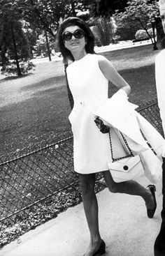 Jackie O chic. White trimmed dress, a matching coat and bag, complete with a natural hairstyle and some shades.