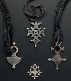 Africa | Four 'crosses' from the Tuareg people of Niger | Silver alloy (Thaler coin silver), some strung on leather