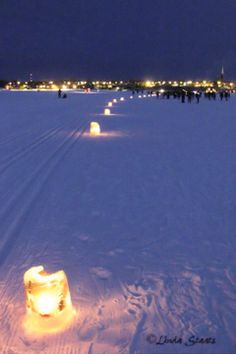 luminaries across frozen Chequamegon Bay to Ashland, WI. The ferry route becomes a highway for cars to drive across the bay in the winter.