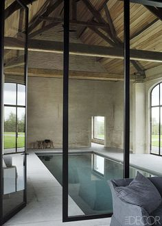 """""""You need these imperfections to surprise people, to make things not too predictable,"""" he says. """"That's the essence of this project. Once you step inside, it's anything but a conventional farm house."""" The poolhouse in a former barn features steel frames and original beams; the pool is sheathed with glass mosaic tiles, and the surround is Belgian bluestone. - ELLEDecor.com"""