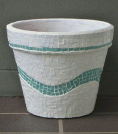 A mosaic garden pot made with white and turquoise tiles. I am planning to grow a lemon tree in it.