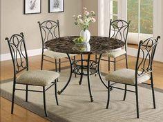 Esta es la mesa que esta el comedor. Esta rodeada da cuatro sillas en metal con almohadas. Sobre la mesa hay un hermoso florero donde siempre ponemos unos flores coloreados.