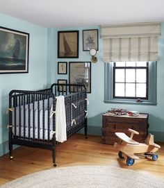 """The owners of this Massachusetts home shopped the Brimfield Antique Show, flea markets, even amazon.com for antiques and classic pieces, trunks, sailboat prints. Painted black for an air of urban glamour—including the spindle crib belonging to their son. """"I didn't want a nursery that screams 'baby,'"""" the owner explains. """"Now, it's my favorite room."""" In this photo: The Jenny Lind crib"""