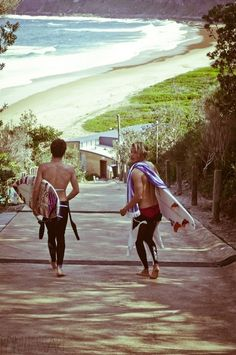 surfers and a beach and wetsuits