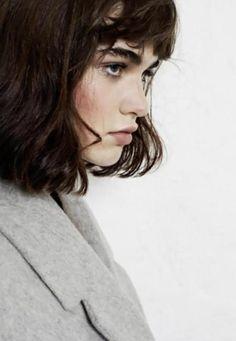 ernst. Mischung aus Gegensätzen (feminin: Wuschelbob, Stirnfransen, wellige Haare / maskulin: kräftige Augenbrauen, Herrenmantel). Find ich gut!