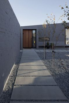 Lake Hawea Courtyard House concrete slab walkway -- With its expansive, geometric design and wide concrete-slab walkways, the enclosed central courtyard around which the house is organized creates outdoor space protected from the sometimes-inhospitable wind out of the northeast.