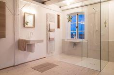 Das Badezimmer im Obergeschoss der Welle8 hat viele Besonderheiten: Vollverglaste Trennwand zum Wohnzimmer, durchgehender Wandvorhang, gekalkter Kiefernboden, weiss lackierte Balken, weisse Armaturen, vollverglaste Dusche, zwei Waschbecken mit Spiegel bzw. im Sprossenfenster nach Süden mit Blick durch die Birnenbäume, doppelte Veluxfenster (Drehpunkt oben) über der Badewanne nach Westen in den Vordergarten. www.welle8.com/ #Bad #Badezimmer