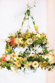 A flower chandelier is the perfect decoration & easy to DIY! One hanging above the centre of each table with trailing flowers hanging down and candles and single stem flowers in votives on the table. Perfection!