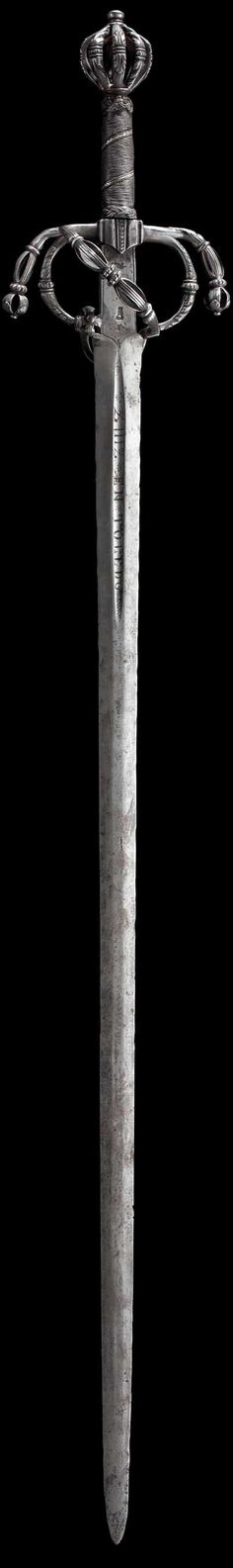 """An Italian sword with cut iron hilt circa 1560/70 Double-edged, flatly ridged blade, the ricasso stamped """"MZ"""" under a crown on both sides. The short groove etched with """"DE FRANCISCO ZUIZ EN TOLEDO"""". Finely cut and open-work iron hilt (loosened, slightly curved up at the ricasso) with pas d'*ne on the reverse side. Iron wire grip traversed by silver and with Turkïs heads. Length 107.5 cm. Lavishly cut hilt. http://www.hermann-historica.de/auktion/images63_max/18973.jpg"""