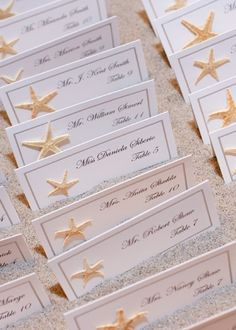 fun beachy escort cards displayed in a box of sand