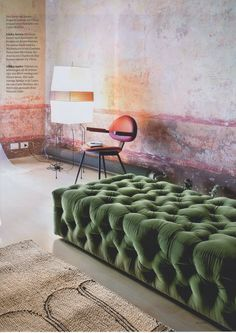 Contrasting textures with a distressed wall and velvet seating.