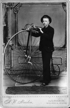 (Circa 1885) Young boy identified as John Reed posed with a high-wheel bicycle. Note that the pedals are attached directly to the front wheel. The wheels became larger as manufacturers realized that the larger the wheel, the farther the cyclist could travel with one rotation.   (Creator: Alden W. Harden)