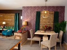 As seen on HGTV's Property Brothers, plum-colored wallpaper and neutral grey paint bring drama to the small eating nook. A square whitewashed wood kitchen table is functional for eating and entertaining. Three wicker chairs complement the table and add texture to the space. The light fixture (made from a brass birdcage) is a romantic twist.