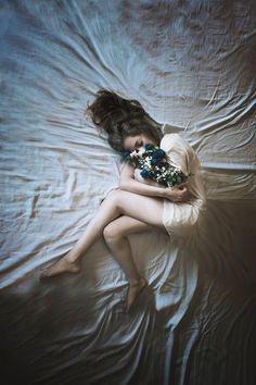 Girl  lying down wrapped in white holding blue roses