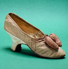 White silk brocade slippers, 1770s, French. Decorated with chocolate-brown ruching and an embroidered floral motif, waisted heels sheathed in white leather, and a white soft leather sole, size 37, Paris, Musée des Arts Décoratifs