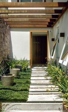 No corredor que leva à porta social, placas de granito Aqualux serrado (20 x 70 cm) foram entremeadas a seixos.