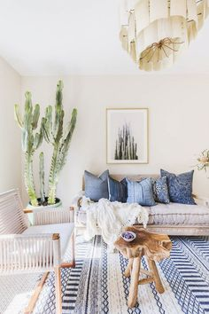 Living room with light neutral walls, a printed blue rug, a large cacti, a reclaimed wood table, and a woven armchair