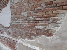 Venetian chipped plaster brick wall