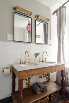 Spectacular bathroom in brownstone with gorgeous gray walls paired with subway tile backsplash framing salvaged wood double washstand with marble countertop and brass gooseneck faucets. Double sink console with his and her sinks and brass picture lights framing black mirrors.