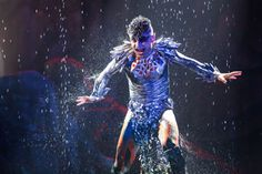 Arial dancing with water raining down around him.