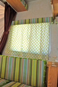 Prettify your camper. She stapled the fabric right over the old ugly stuff. Used sheets for curtains… brilliant! and cheap!